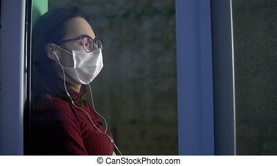 A young woman is sitting at home in quarantine with ...