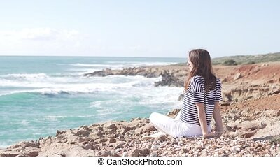 A young woman is sitting on a rock by the ocean