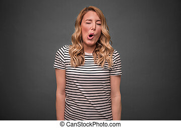 A young woman is squinting a sour grimace while standing...