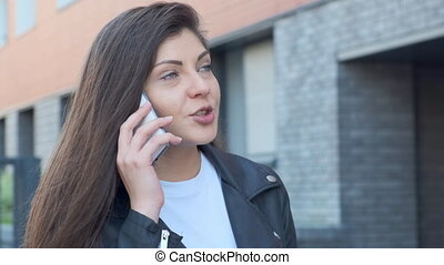 A young woman is talking on the phone