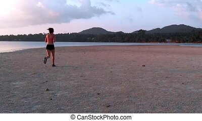 a young woman jogging at the beach on sunset. aerial drone shot, slow motion
