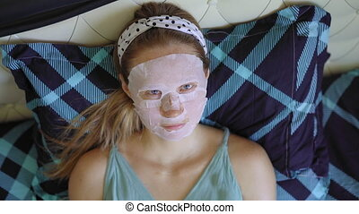 A young woman laying on a bed with a cosmetical face mask on her face. Skincare concept.