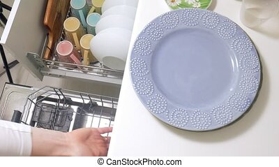 A young woman lays a clean dish from a dishwasher 4k