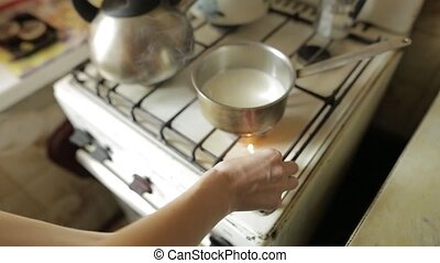 A young woman lights of a gas cooking plate with matches on the kitchen. Girl heating milk in a pan for oatmeal. Cooking process.