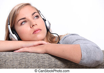 A young woman listening to music on a sofa.