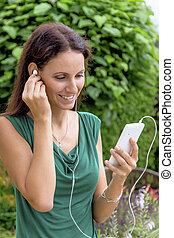 woman listening to music on mobile phone - a young woman ...
