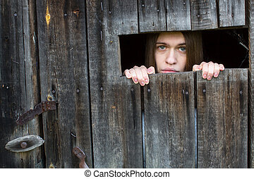 A young woman, locked in a wooden shed.