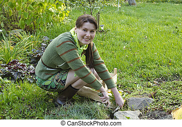 A young woman looks after the alpine slide in the garden