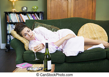 A young woman lying on her couch drinking wine