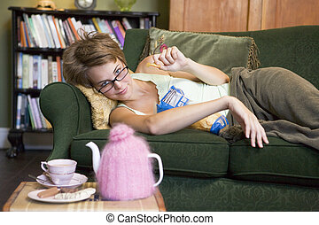 A young woman lying on her couch eating