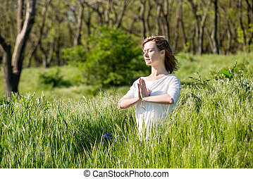 A young woman meditating in park