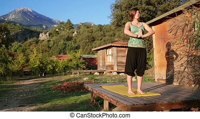 a young woman meets dawn and does Yoga on the veranda of a...