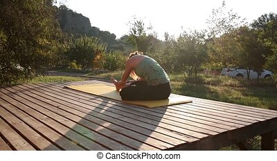 a young woman meets dawn and practices Yoga on the veranda...
