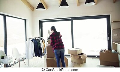 A young woman moving in new home, carrying a box. Slow motion.
