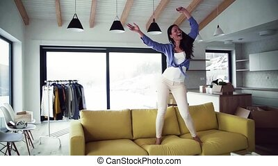 A young woman moving in new home, dancing on sofa. Slow...