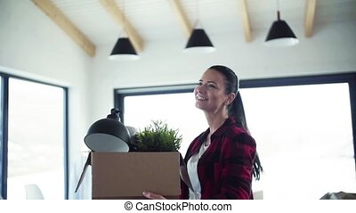 A young woman moving in new home, holding a box. Slow motion.