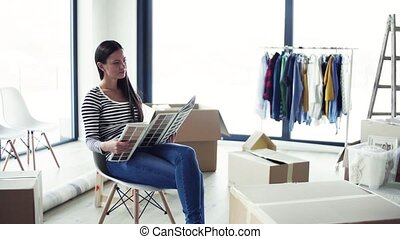 A young woman moving in new home, looking at color swatch.