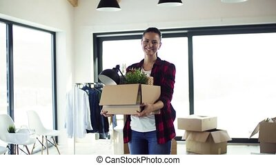 A young woman moving in new home, unpacking stuff. - A young...