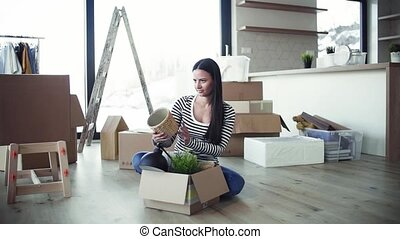 A young woman moving in new home, unpacking stuff. Slow motion.