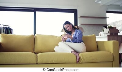 A young woman moving in new home, using smartphone.