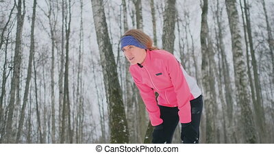 A young woman on a morning jog in the winter forest was...