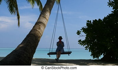 A young woman on a swing makes a selfie. Beautiful beach and turquoise ocean.