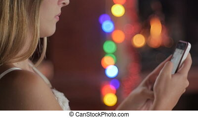 A young woman on her phone turns and smiles at the camera during the holidays