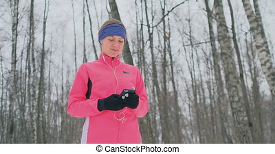 A young woman on the morning jog holds in her hands a...