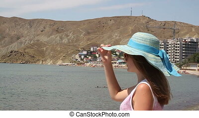 A young woman on vacation at the beach against the sea and the city.