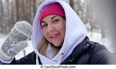 A young woman on winter vacation communicates via video link surrounded by a snowy landscape. A woman, in a winter forest during the Christmas season, takes a selfie video. Slow motion.