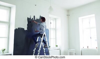 A young woman painting wall black. A startup of small...