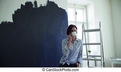 A young woman painting wall black, drinking coffee. A...