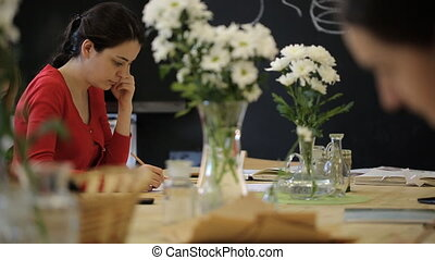 A young woman paints a still life of glass vases with white...