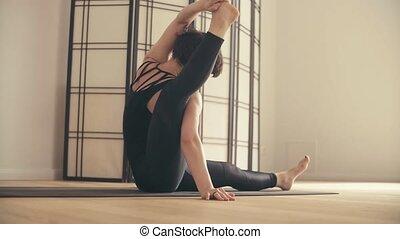 A young woman performing yoga-asanas in the hall. Eka pada...