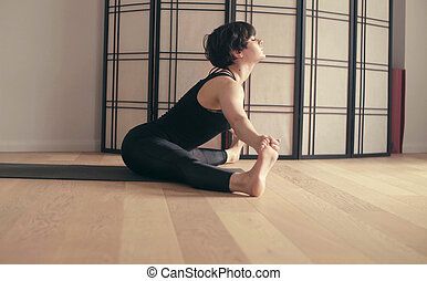 A young woman performing yoga-asanas in the hall. Prasarita...