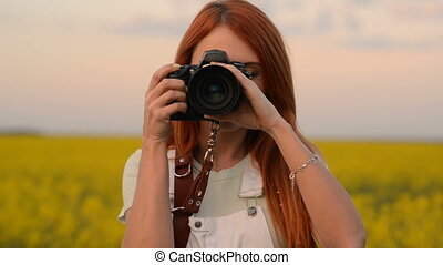 A young woman photographer takes a picture in a blooming field and smiles