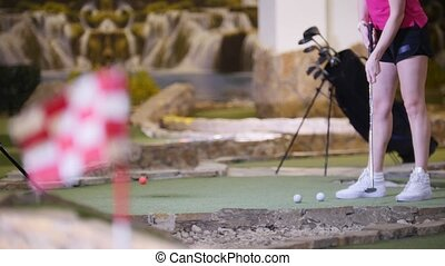 A young woman playing mini golf. A woman hitting the golf...