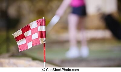 A young woman playing mini golf. Finishing flag on the...
