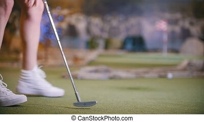 A young woman playing mini golf indoors. Legs in the frame....