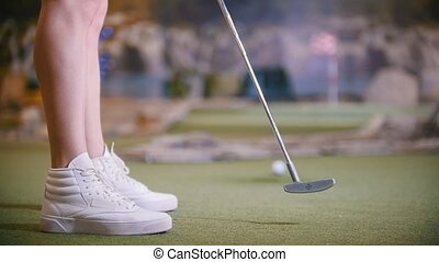 A young woman playing mini golf indoors. Legs in the frame