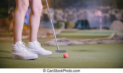 A young woman playing mini golf. Legs in the frame. Mid shot