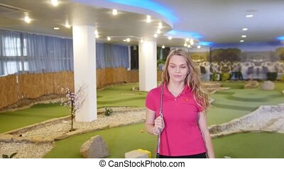 A young woman playing mini golf. Walking on the field. Mid...