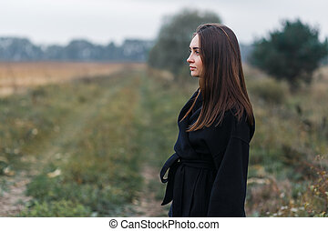 A young woman portrait with village grass road on background. Cloudy autumn weather