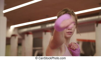 A young woman practising karate indoors in gym. Copy space.