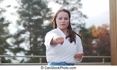 A young woman practising karate outdoors on terrace.