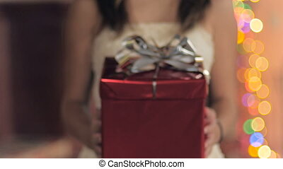 A young woman presents a red wrapped gift with a silver bow towards the camera