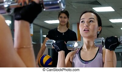 A young woman pumps her hand muscles with a dumbbells....