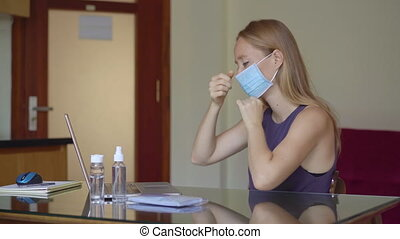A young woman puts on a medical face mask and works from home during coronavirus self-isolation