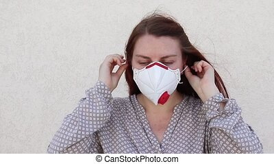 Young woman puts on a medical mask to protect against viruses, germs, dust or polluted air. Coronavirus and Covid-19 concept