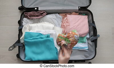 A young woman puts things in a suitcase